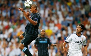 Manchester City's Vincent Kompany goes for a header in front of Real Madrid's Sami Khedira during their Champions League Group D soccer match at the Santiago Bernabeu stadium in Madrid